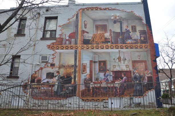 mural on the side of a two storey white brick building.  The picture looks like the outer wall has been removed to reveal a family house from the early 1900s.  A cook is working in the kitchen,