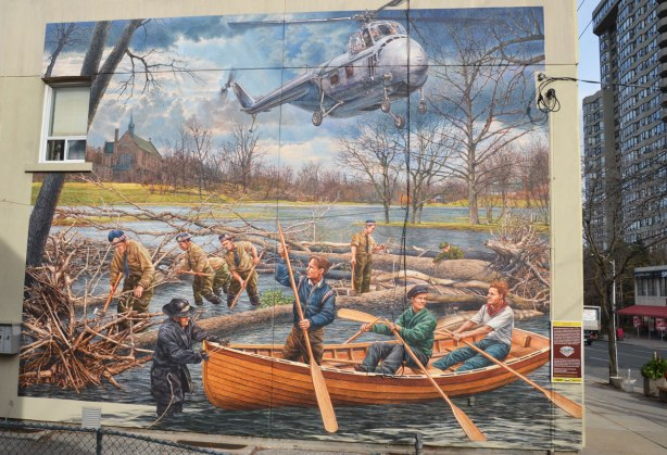 large painting of men in boats, helicopter overhead