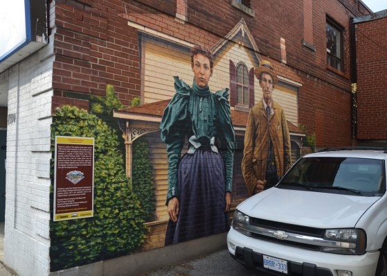 A mural of a man and a woman standing outside a two stroey farm house.  A white car is parked in front of the mural and it blocks the bottom right of the picture.