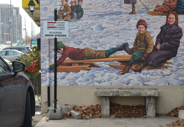 Close up of the bottom part of a mural whowing kids on old fashioned wooden sleds, or toboggans.