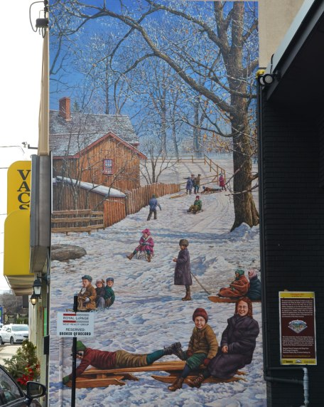 large vertical mural depicting a hill in winter.   Bare trees, kids on tobaggons.