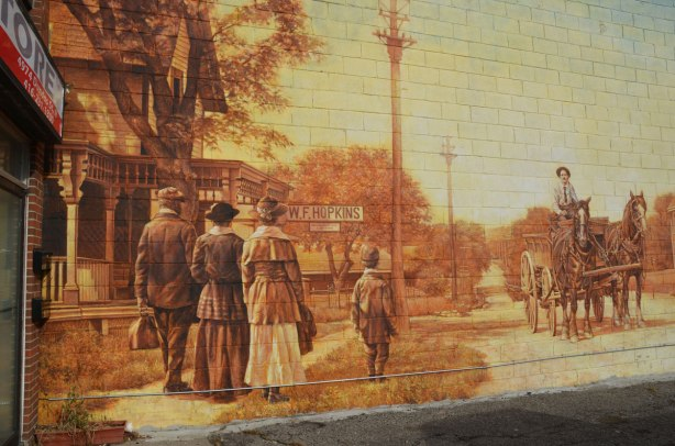 part of a large mural on the side of a building that shows people in old fashioned clothes walking down a street.  A man in a horse drawn wagon is coming down the street.