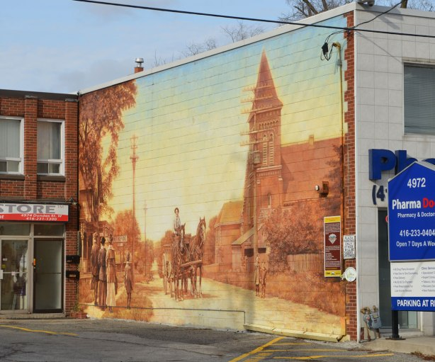 large mural on the side of a building that shows people in old fashioned clothes walking down a street.  A man in a horse drawn wagon is coming down the street.