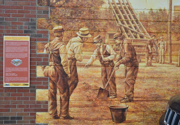 a mural showing a group of men in clothing from the 1930s shoveling in the dirt.