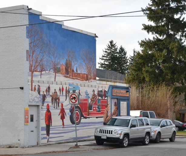 looking across the street at a mural on the side of white brick building, a winter scene, some people are skating, lots of bright red jackets, there is also an old fashioned fire engine with firefighters sitting in it.  At the right edge of the picture is a small wood hut with a sign that says Refreshments on it.