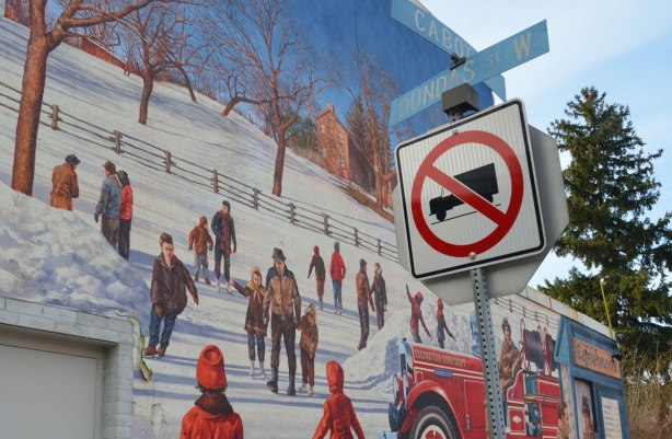 close up of a mural showing people skating on a frozen pond in the winter.  In the foreground is a traffic sign that says no trucks, also blue street signs for Cabot St. and Dundas Street West