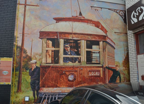 A mural showing the front of an old electric train car with the conductor sitting in front.  Two boys are hanging out the doors, one on each side of the train car.