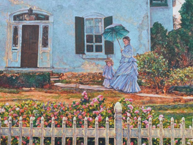 A woman and a girl in long light blue dresses are walking in front of a house.  The woman is carrying a blue parasol.  There is a white picket fence and flowering shrubs in the foreground of the picture.