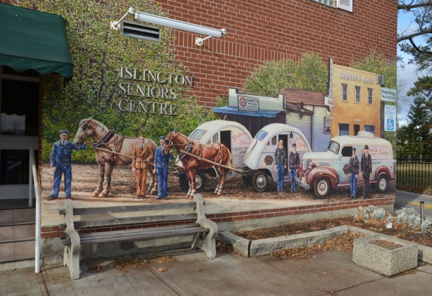 A mural on the front of the Islington Senior's Centre showing dairy carts.