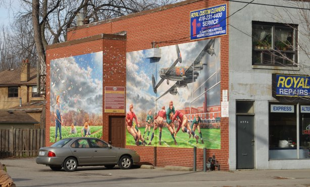 mural showing men playing football in the 1920s, with a low flying airplane overhead, as seen from an angle - form this perspective you can see that the mural is actually two pictures.