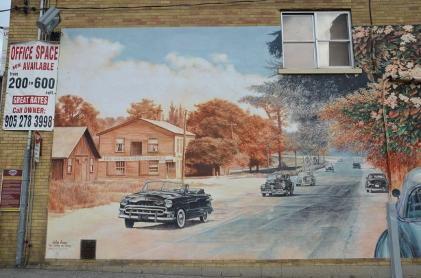 part of a mural depicting the main street of town as it was in the 40s and as it was in 2006.  cars, street, people shopping,