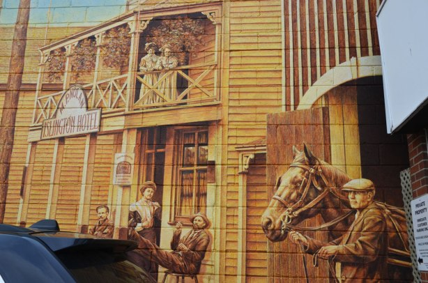 part of a mural, a man leading a horse out of the stables, the Islington Hotel behind.  Two ladies are standing on the balcony of the second floor of the hotel.  A man is reclining on a chair on the front porch of the hotel.