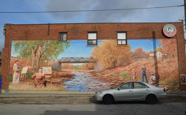 A large mural of a creek.  On the left back are two painters with their easels set up beside the river.  On the right bank are two boys and a man