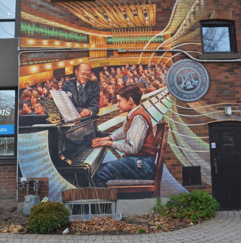 mural depicting a boy playing a piano in front of an audience.  A man is helping to turn the pages of the music.
