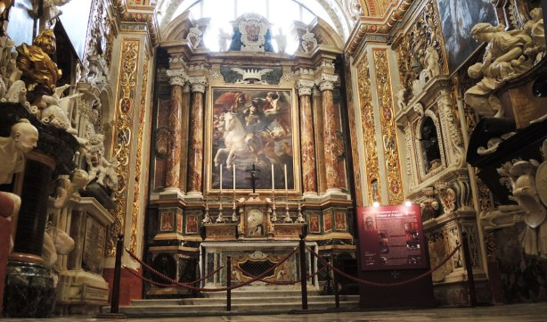 A chapel in a cathedral.  An altar with six very tall candles in front of a large painting of a man on a white horse.  The rest of the chapel is very ornately decorated.