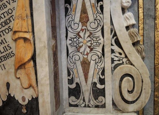 Detail of stone work on a wall.  Swirls, flower, words