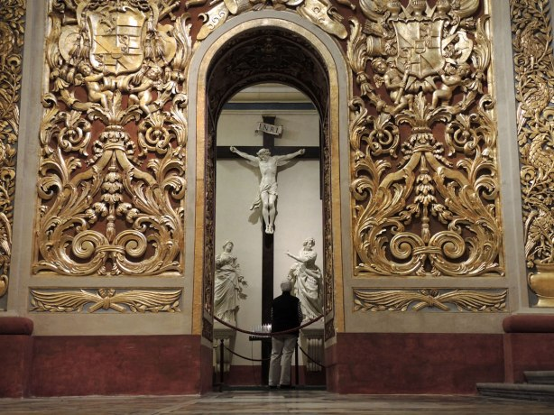 Looking across a large room with ornate gold walls towards an archway that leads to another room.  In the room beyond there is a large marble crucifix with marble statues on either side of it.  A person is standing looking at the crucifix with their back to the camera