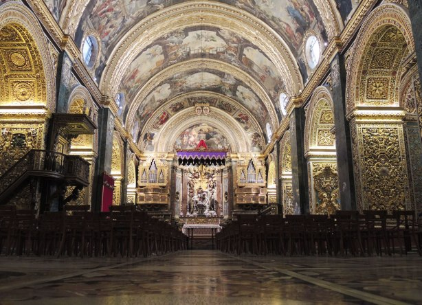 Looking down the nave towards the main altar of a very decorated cathedral