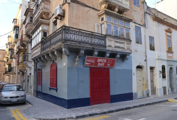 A building on the corner of an intersection.  It is light blue with a dark blue band around the bottom near the sidewalk.  The doors and two windows are covered with red shutter.  A coke sign is above the door - the sign is horizontal and also has the name of the bar written in white letters, Bros Bar.
