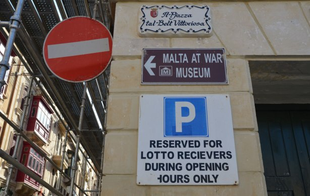 Four signs on the side of building.  A red and white circular no entry road sign, a street name sign, a sign pointing towards the Malta at War Museum, and a reserved parking sign on which there is a spelling mistake.
