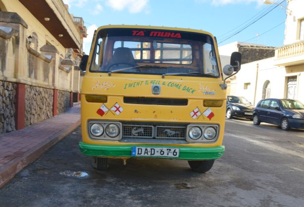 yellow van parked on the side of a street.  The first three letters of the licence plate are D A D which spells dad.  The words 'I went to hell and come back' are written across the front of the van.