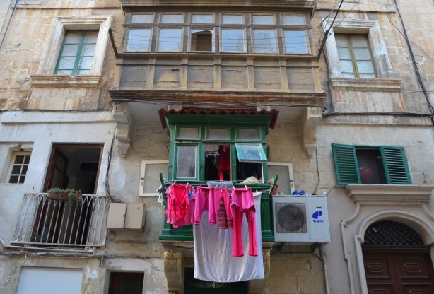 Laundry hanging from a balcony in Valletta Malta, limestone buildings and painted shutters.