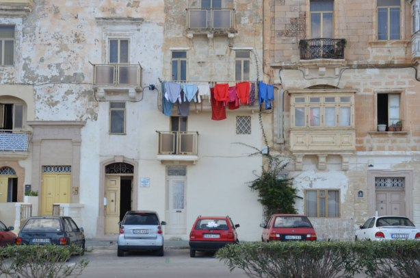 Laundry hanging from a balcony in Valletta Malta, limestone buildings and painted shutters.  Four small cars parked beside the building.