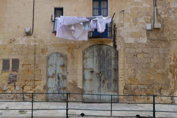 Laundry hanging from a balcony in Valletta Malta, limestone buildings and wooden shuttered doors