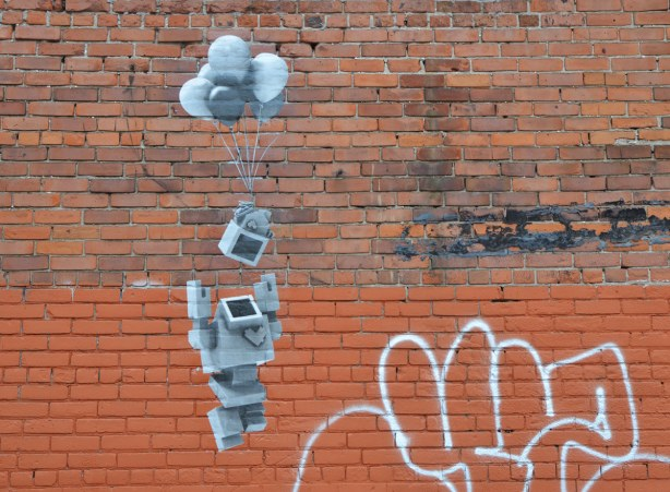 Lovebot on a red brick wall with his arms out stretched as he releases a box into the air.  The box is being lifted upwards by balloons.