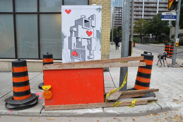 lovebot playing card on a wall.  In front of it are some orange and black traffic cones along with an orange construction sign on its side.