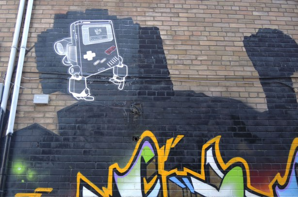 Lovebot in the shape of an old gameboy, up on a brick wall, with tags below him.