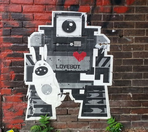 A lovebot on a red brick wall.  A small white oval shaped figure is with him.