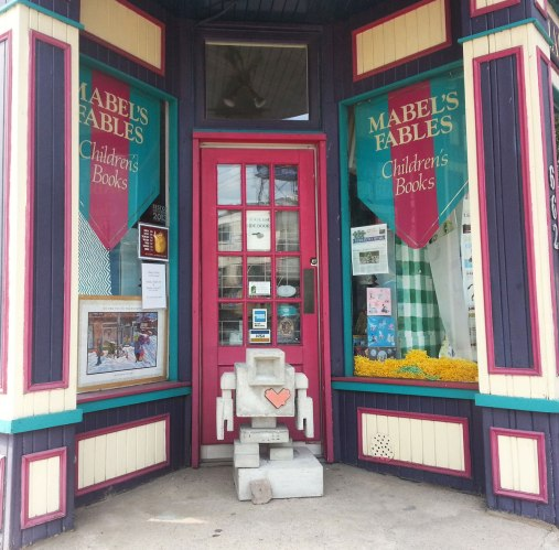 A small concrete lovebot stands in the doorway of a childrens book store called Mabels Fables.