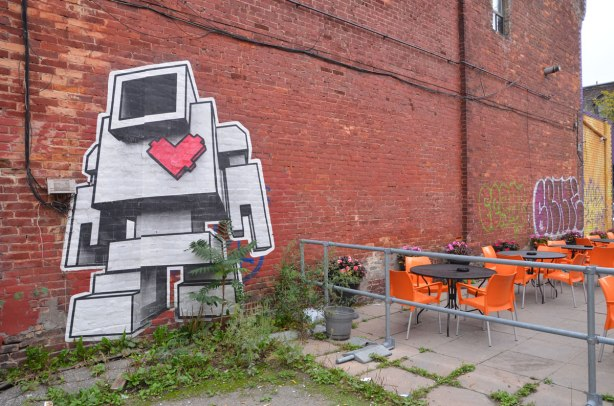 A very large lovebot on a brick wall.  He looks like he is walking away from a restaurant patio with its black round tables and bright orange chairs.