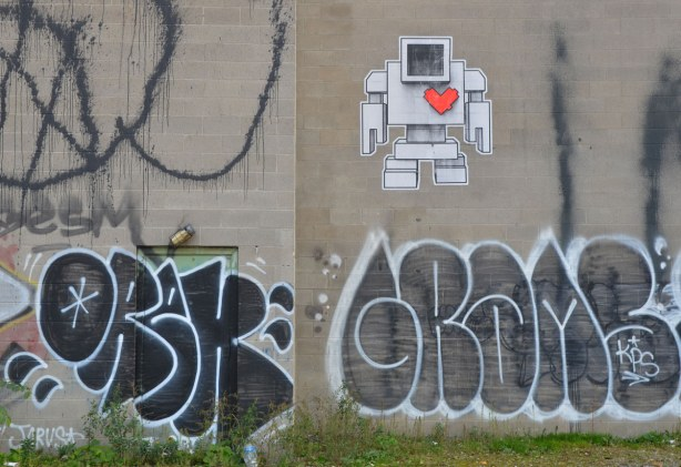 Wheatpaste lovebot up high on a concrete wall.  There are some black and white tags below him.