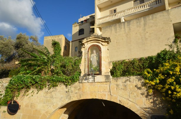 The top part of a rounded stone arch with a stone case with a Mary statue in it.  The case has a glass front.