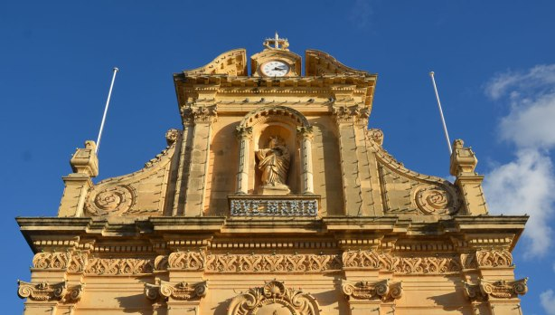 The top part of the front of a limestone church with a statue of Mary in a niche.