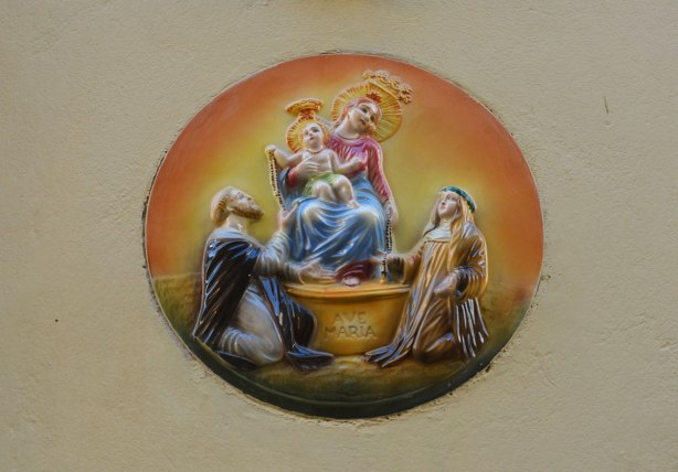 A round medallion of Mary holding the baby Jesus on a raised surface.  Two men are kneeling below and looking up towards mother and child