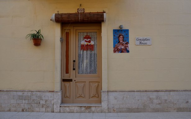 Doorway, wood door on pale yellow house.  plant on wall on one side of the door, a picture of Mary on the right.  A Santa decoration is on the door.