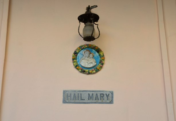 A round medallion of Mary and the baby Jesus, with the words 'Hail Mary' in grey beneath.  A light is above the medallion.