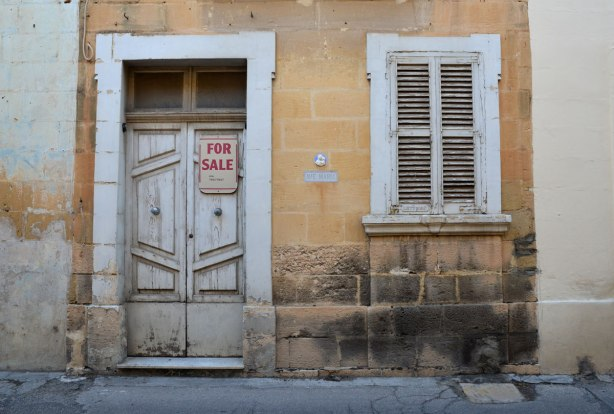 House for sale.  An old grey door and old grey shutters on a wondow.  For Sale sign on the door.