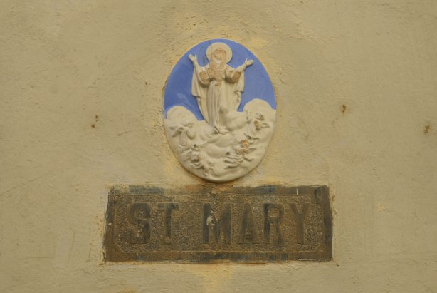 A blue and white oval shaped medallion of Mary standing on a cloud.  The words 'St. Mary' are in brown underneath.