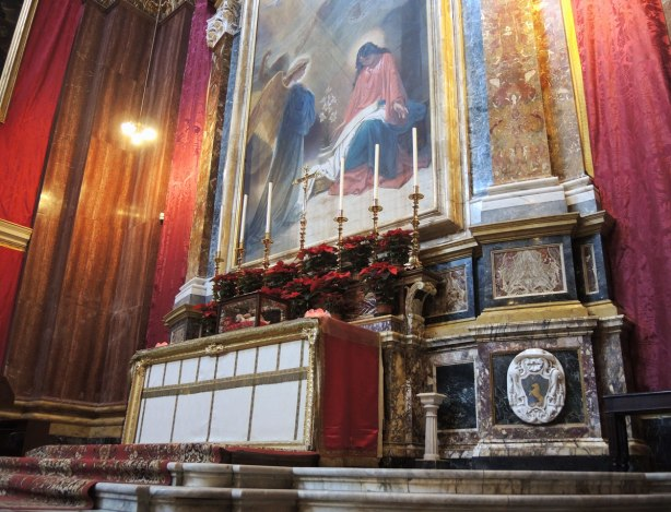 altar with tall candles and poinsettias for Christmas.  A large religious painting is above the altar.