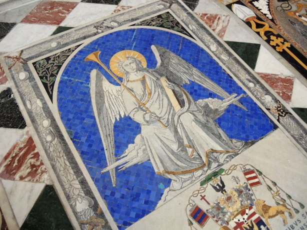 Tiles on the floor of the cathedral, close up of an angel on a blue background.
