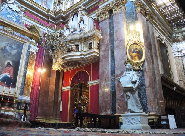 interior of the cathedral in Mdina, statues and stone work.  Parts of the walls are covered in red fabric.
