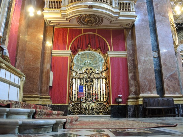 Interior of the cathedral, carpet on a few stairs, a metal gate in front of a side chapel, some walls covered in red fabric, marble work,