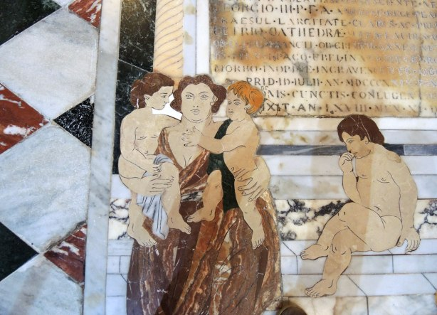 Mosaic tile work on the fllor - a woman holding two children while another woman sits on stone steps.  There are also words in the picture.