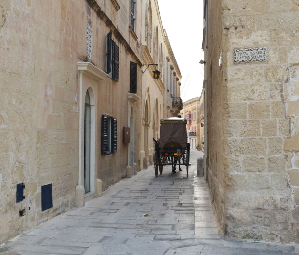 horse drawn carriage passes through a narrow lane, yellow limestone buildings on either side.