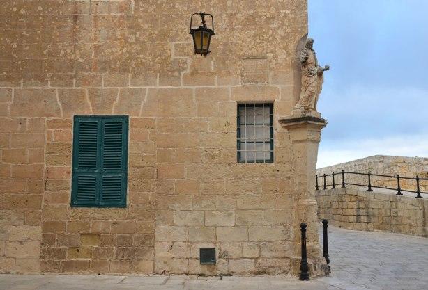 Small stone religious statue on the corner of a limestone building.