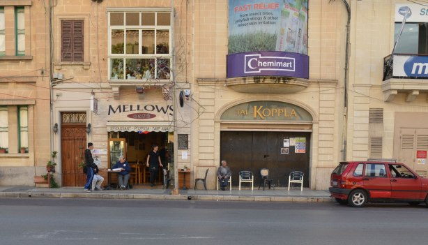 looking across the street to Mellows, a restaurant and pizzeria.  There are people sitting at tables outside on the sidewalk.   Beside Mellows is a store called Tal-Koppla but it is closed up.